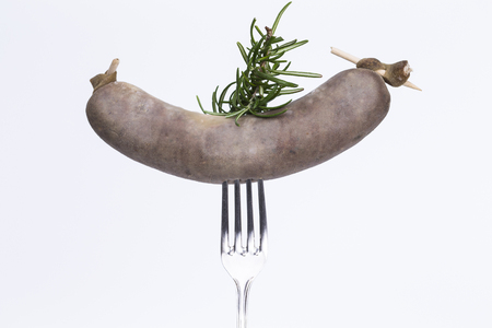 smoked sausage: Image shows a fork with a smoked sausage isolated on white background