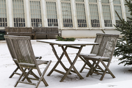 The photo shows snow-covered garden furniture Фото со стока