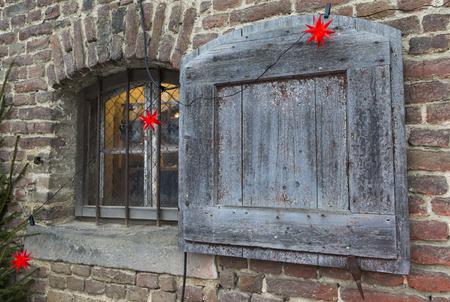 Das Foto zeigt ein weihnachtlich, geschmücktes Fenster mit Laden. Der Fensterladen bietet Platz für Text