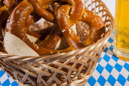 The photo shows a bread basket with fresh pretzels and a glass of beer