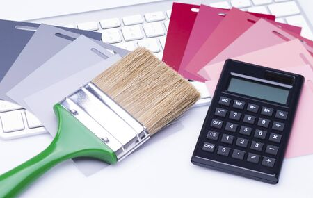 The photo shows various color cards with a flat brush and a calculator on a keyboard Standard-Bild