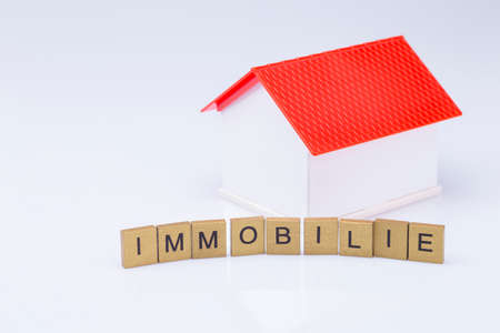 The photo shows a white model house with red roof and wooden letters Standard-Bild