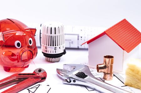 Image shows a red piggy bank with a model house, floor plan and various tools, isolated on a white
