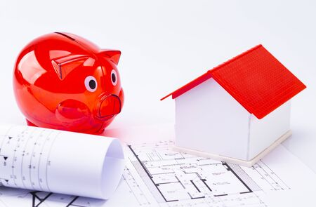Red piggy bank with a model house and floor plan, isolated on a white