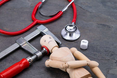 Image shows a wooden puppet with clamp and stethoscope Standard-Bild
