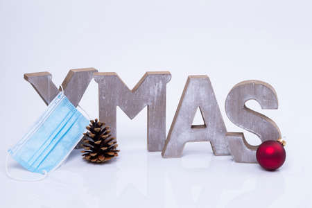 The photo shows the word X-Mas written with wooden letters with protective mask, cone and Christmas ball Standard-Bild