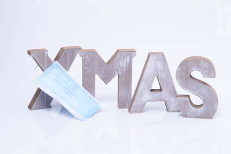 The photo shows the word X-Mas written with wooden letters isolated on white