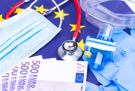 The photo shows a mouth and nose protector with disposable gloves, Cash and a stethoscope on a European flag