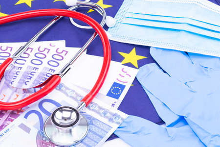 The photo shows a mouth and nose protector with disposable gloves, cash and a stethoscope on a European flag Standard-Bild