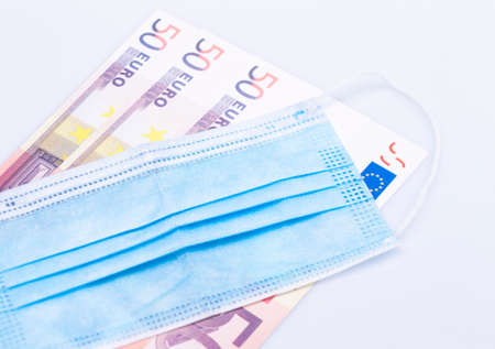 The photo shows a safety mask with banknotes, synonymous with wearing a safety mask