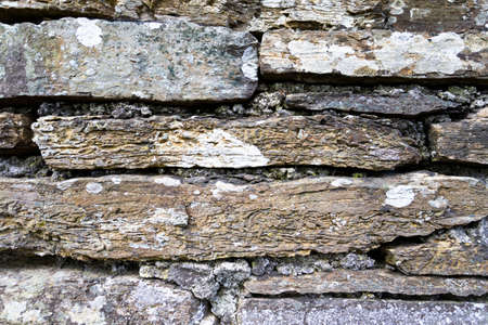 The photo shows a rustic stone wall in daylight Foto de archivo