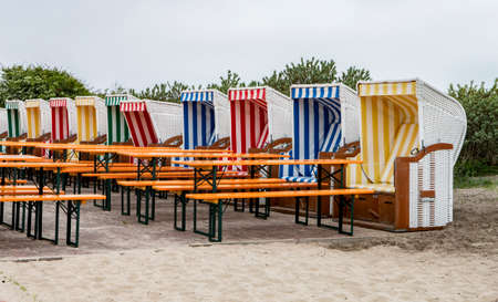 Several beach chairs with tables and benches in a restaurant on Baltrum
