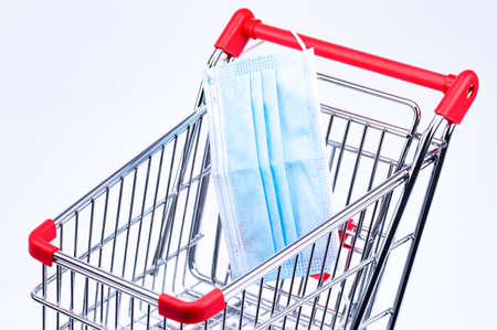A shopping trolley in detail with a mouth and nose protection Standard-Bild