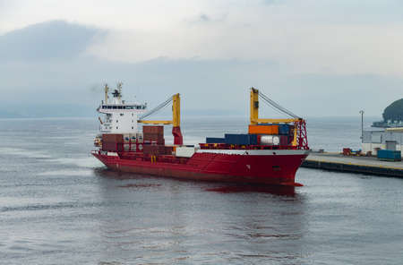 The photo shows a cargo ship docking in the harbor of Bergen