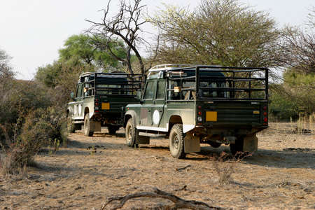 four wheel: Two four wheel drives of an expedition parking in the bush next to a dry riverbed in Namibia, Africa
