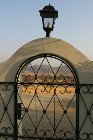 leading light: Garden doorway of a namibian guesthouse leading to the wilderness in the early morning light