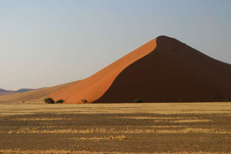 majestic red dune at the end of a wide plain photo