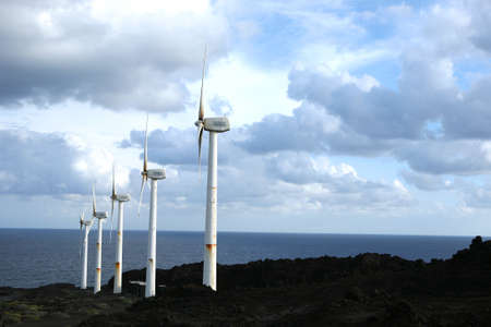 A row of wind wheels at the coast of a volcanic island generating clean power in front of a stormy sky photo