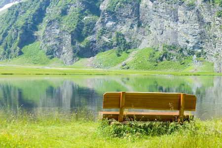 wooden bench in front of a beautiful mountain lake photo