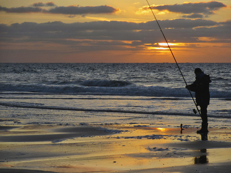 Sunset on the sea with angler