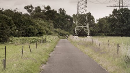 A cyclist passes a high voltage pylon on a road in the meadows.