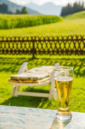 Beerglass and lounger in front of a garden fence. High mountains in the background.
