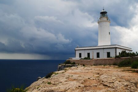 Far de la Mola, lighthouse on the cliffs of Formentera an approaching storm. Stockfoto - 132043317