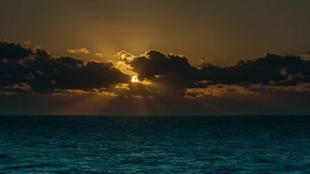 Setting sun shines through the clouds over a cyan Caribbean Sea.