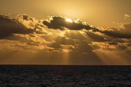 Sun sends sunbeams to the Caribbean Sea.