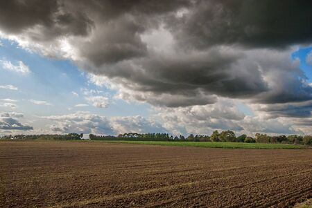 Dramatic rain clouds over a harvested field. Stok Fotoğraf