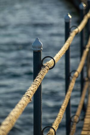 Rope railing of a landing stage in the evening light. Backlit, Scene from Egypt.