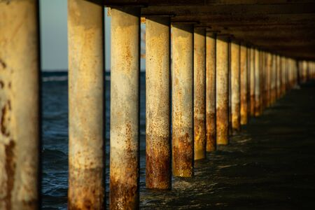 View under a jetty on a sunny evening.
