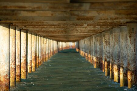 View under a jetty on a sunny evening. Focus close. Stock Photo
