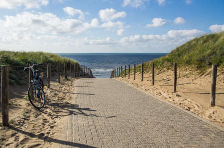 Way to the beach over the cordoned off dunes, a parked bike on the side.