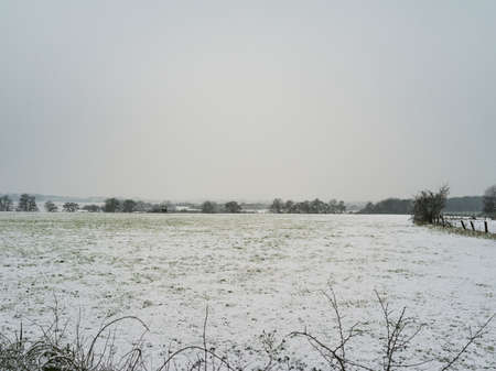 Snow-covered fields on a cloudy morning.