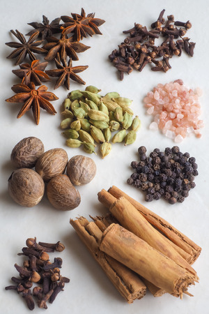 cinnamon bark: Spices with Pink Salt. A selection of spices - cloves, cinnamon bark, black pepper corns, whole nutmegs, cardamom pods, star anise - with pink rock salt crystals.