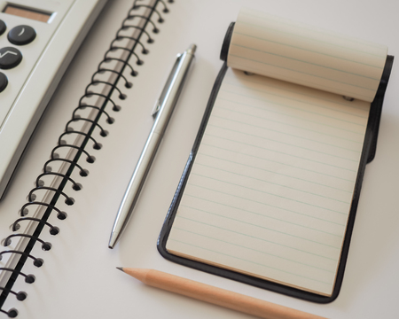 spiral binding: Note Pad with Calculator. A small note pad, on a larger spiral bound sketch pad, with a silver cased pen, a plain lead pencil and a calculator.