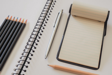spiral binding: Note Pad with Colored Pencils. A small note pad, on a larger spiral bound sketch pad, with a silver cased pen, a plain lead pencil and a group of colored pencils.