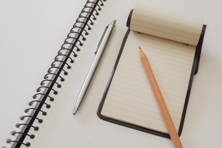 spiral binding: Note Pad with Pen and Pencil. A small note pad, on a larger spiral bound sketch pad, with a silver cased pen and a plain lead pencil. Stock Photo