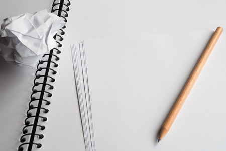spiral binding: Blank note paper on an open spiral bound sketch book, with a piece of crumpled paper and a lead pencil.