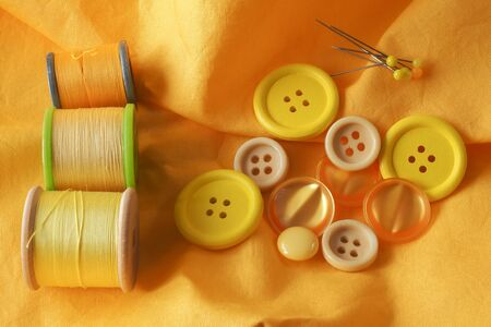 haberdashery: A collection of haberdashery items with a yellow theme - buttons, dressmakers pins and cotton on bobbins. All on a piece of yellow fabric. Stock Photo