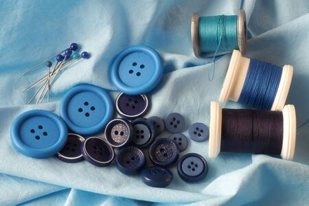 haberdashery: A collection of haberdashery items with a blue theme - buttons, dressmakers pins and cotton on bobbins. All on a piece of blue fabric.