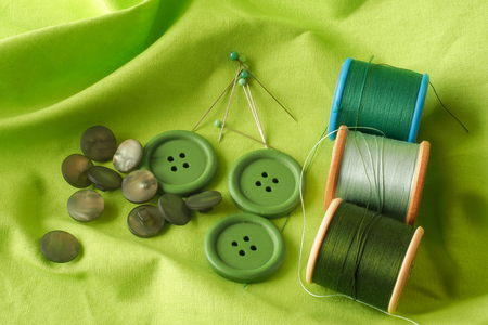 haberdashery: A collection of haberdashery items with a green theme - buttons, dressmakers pins and cotton on bobbins. All on a piece of green fabric.