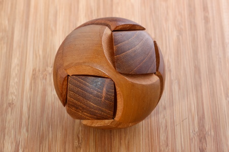 Wooden ball puzzle on wooden background