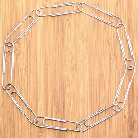 Paper clips linked in a ring on wooden background Stock Photo