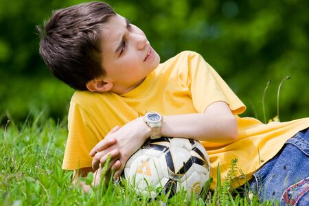 Cute kid resting in meadow after soccer game photo