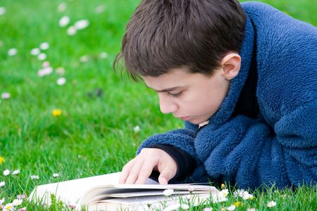 grassfield: Teenager reading in a grassfield