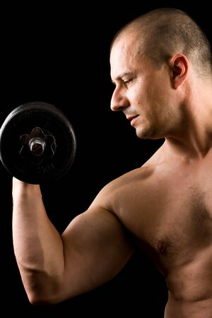 handsome man lifting weights isolated on black photo