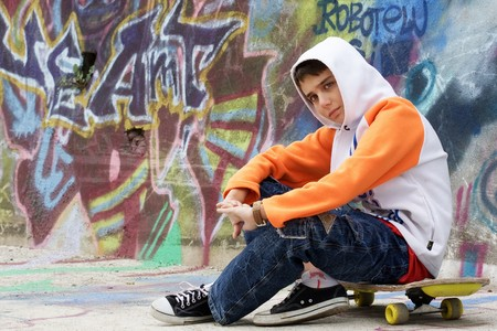 retrospective: Retrospective teenager sitting near a graffiti wall Stock Photo