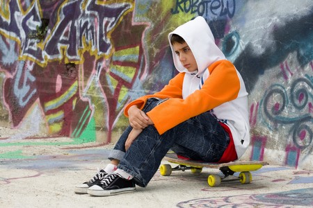 lonely boy: Angry teenager sitting on his skate near a graffiti wall
